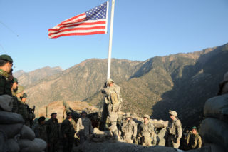 A noncommissioned officer with Troop C, 1st Squadron, 32nd Cavalary Regiment, prepares to lower the American flag during a transfer of authority ceremony at Observation Post Mace, as U.S. and Afghan National Army Soldiers look on. The ANA assumed control of OP Mace from the U.S. Army on Dec. 20. OP Mace is the northernmost observation post in Afghanistan's Kunar Province, which borders Pakistan. It is the first significant installation in the province for which ANA forces have assumed complete responsibility. ANA soldiers now safeguard the post and surrounding area, in accordance with the way ahead laid out in the Lisbon Plan to transfer security responsibility to Afghan forces. (U.S. Air Force Photo by Capt. Peter Shinn, Task Force Bastogne Public Affairs/RELEASED)